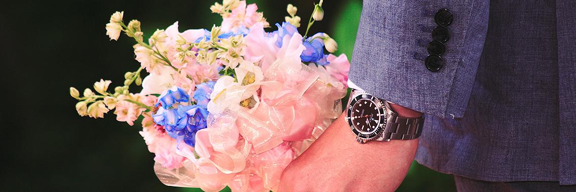 Man holding flowers waering a fancy watch
